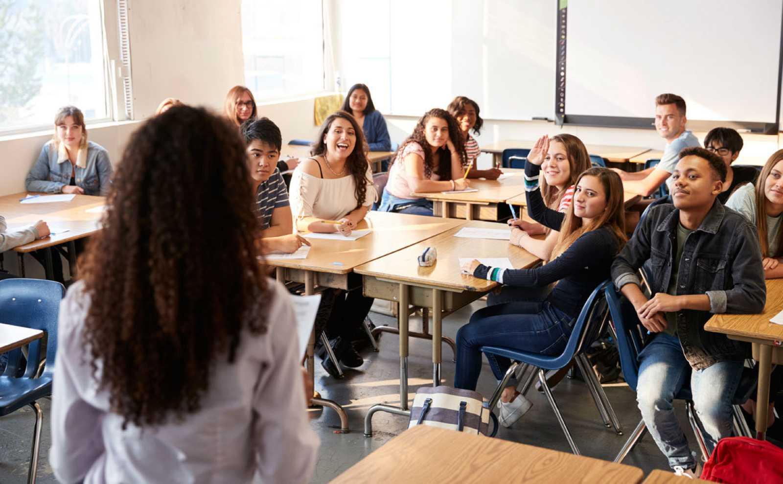 Una profesora imparte clase a un grupo de adolescentes en el aula.