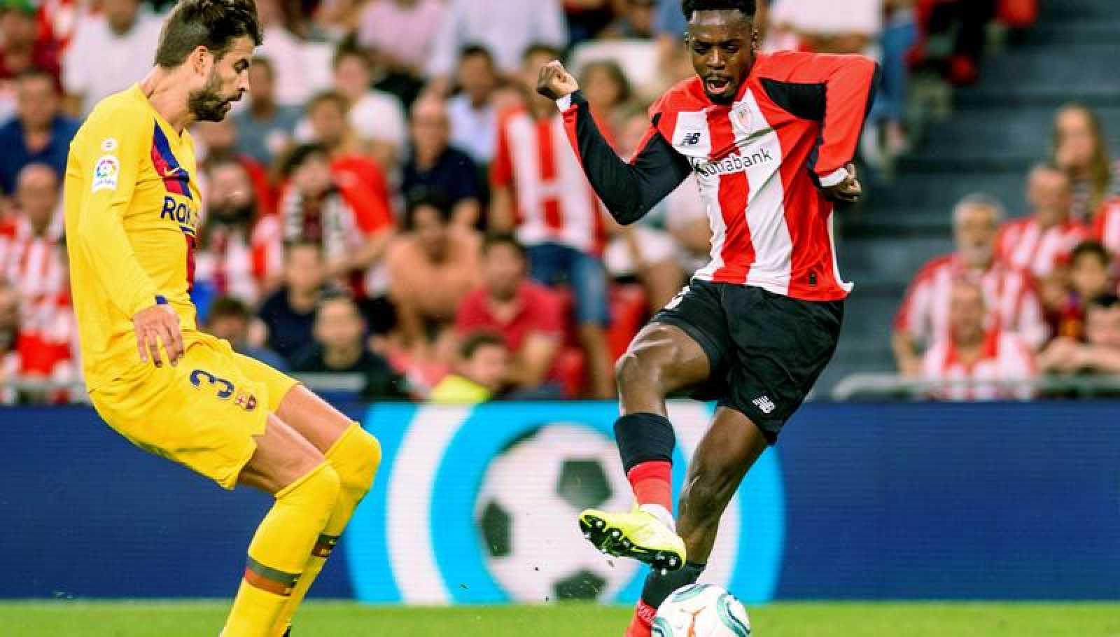 El jugador del Athletic Club de Bilbao Iñaki Williams (d) remata ante la oposición del central del FC Barcelona Gerard Piqué en el partido de Liga del 16/08/2019