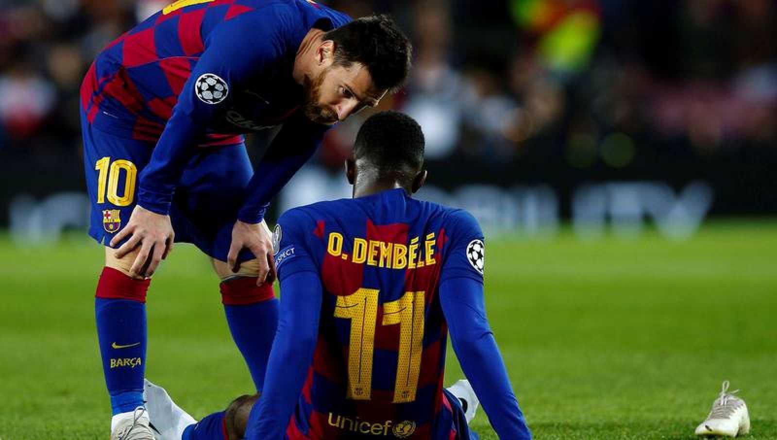 El delantero francés del FC Barcelona, Ousmane Dembélé (d), conversa con su compañero Leonel Messi (i) antes de ser sustituido aquejado de unas molestias