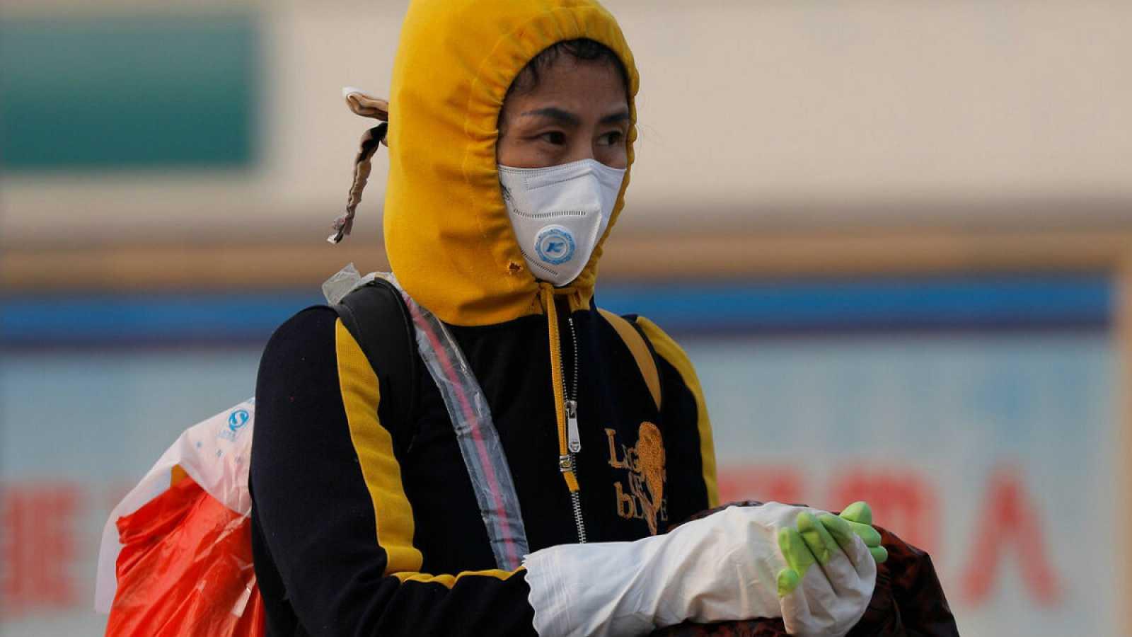 Cerca de la estación de tren de Pekín, una mujer se protege con mascarilla y guantes ante el coronavirus.