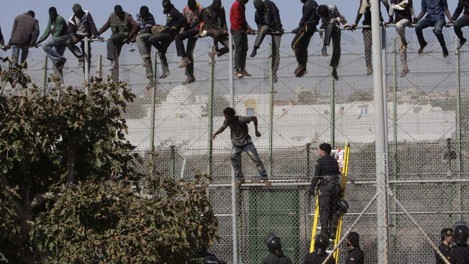 Un grupo de migrantes subsaharianos encaramados a la valla de Melilla en 2015