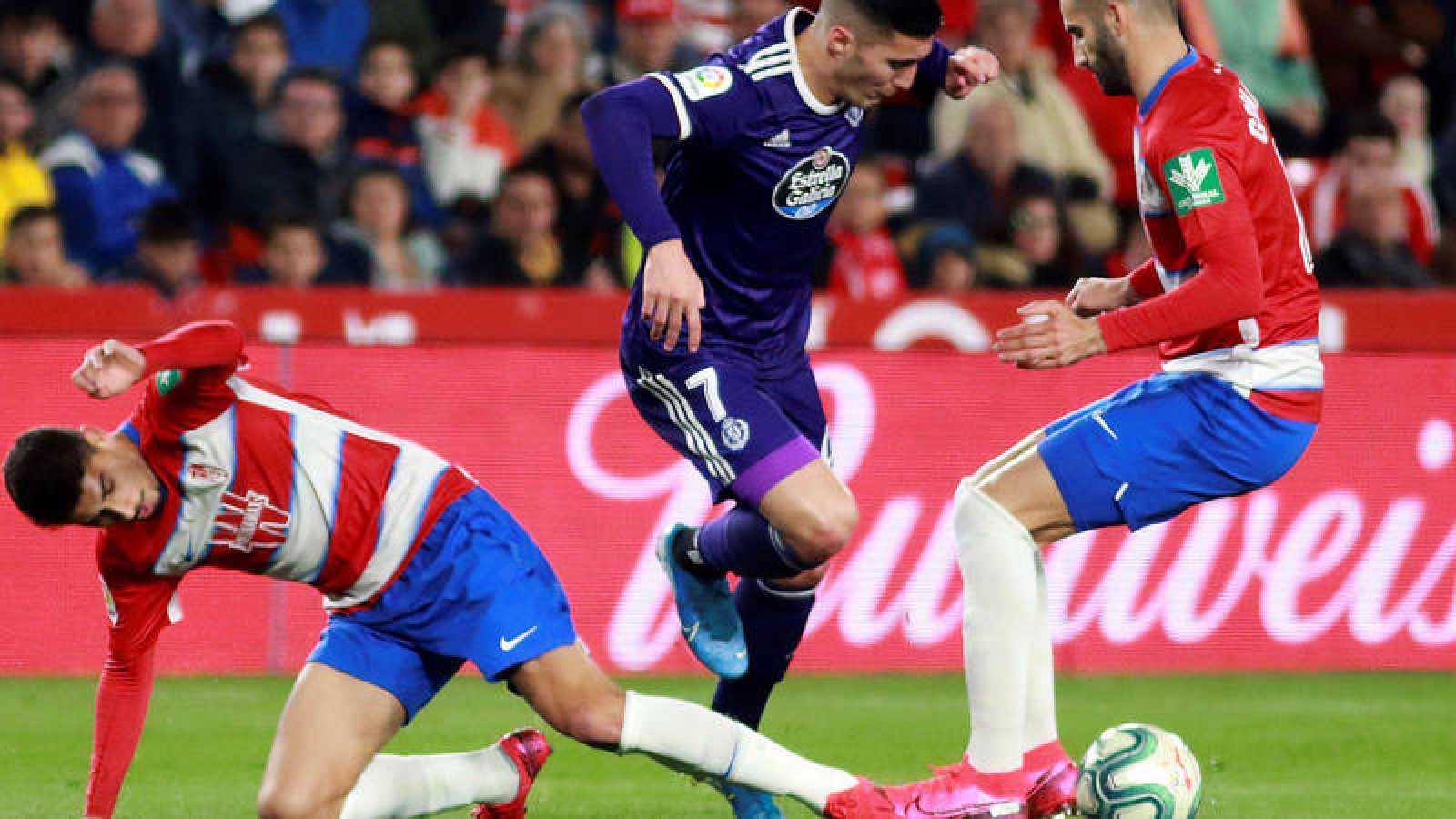 El delantero del Valladolid Sergi Guardiola (c), entre dos jugadores del Granada