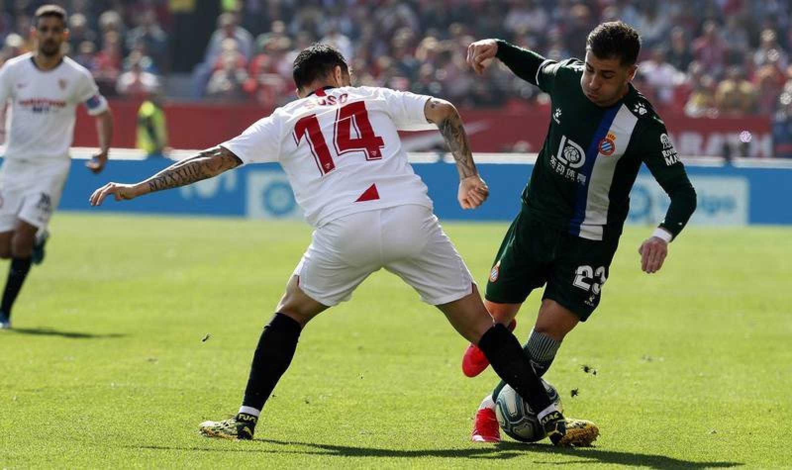 El delantero del Espanyol Adrián Embarba (d) trata de marcharse del centrocampista del Sevilla Suso Fernández (i),