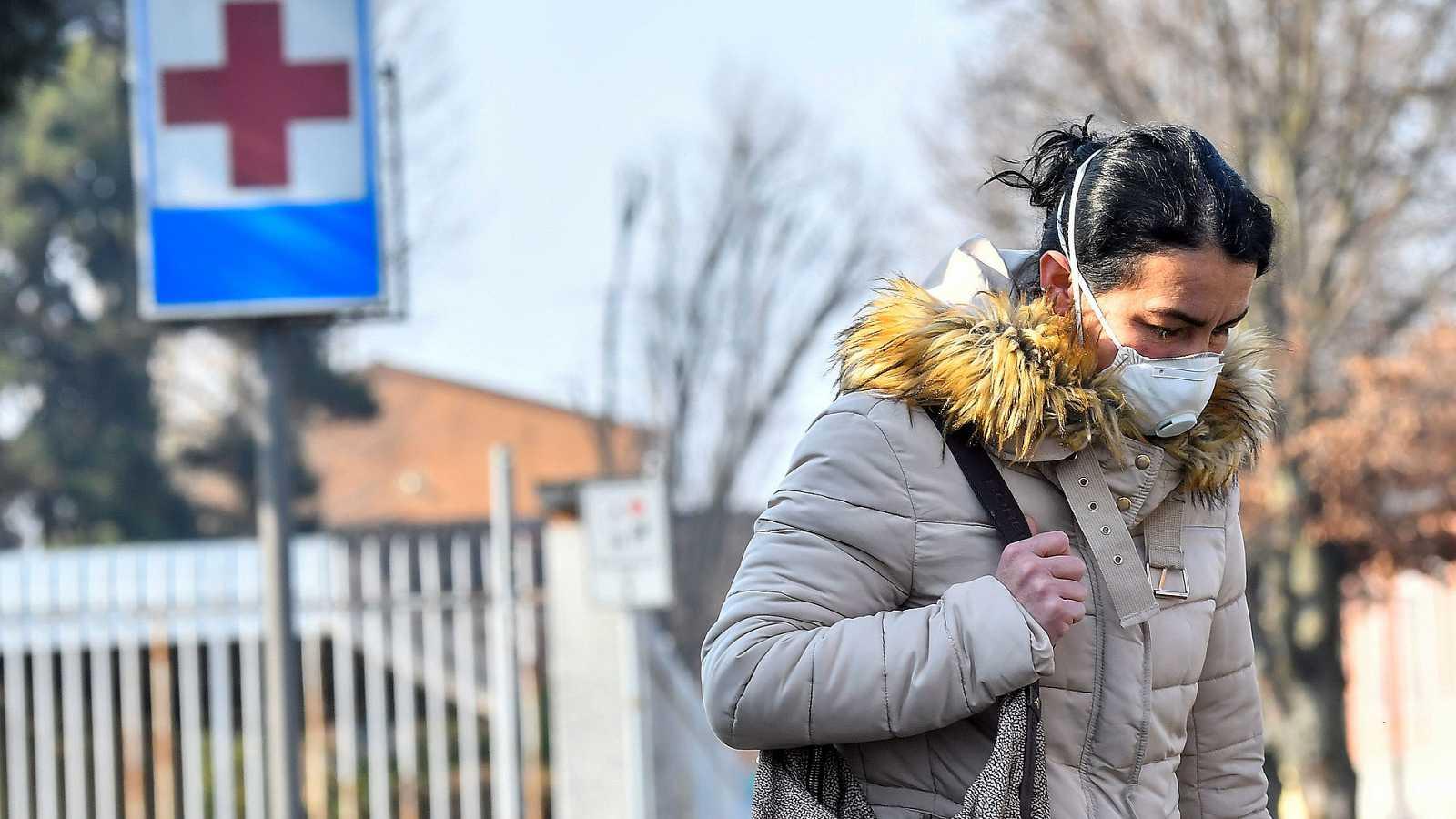 Una mujer con mascarilla sale del hospital de Codogno, foco del coronavirus en Italia