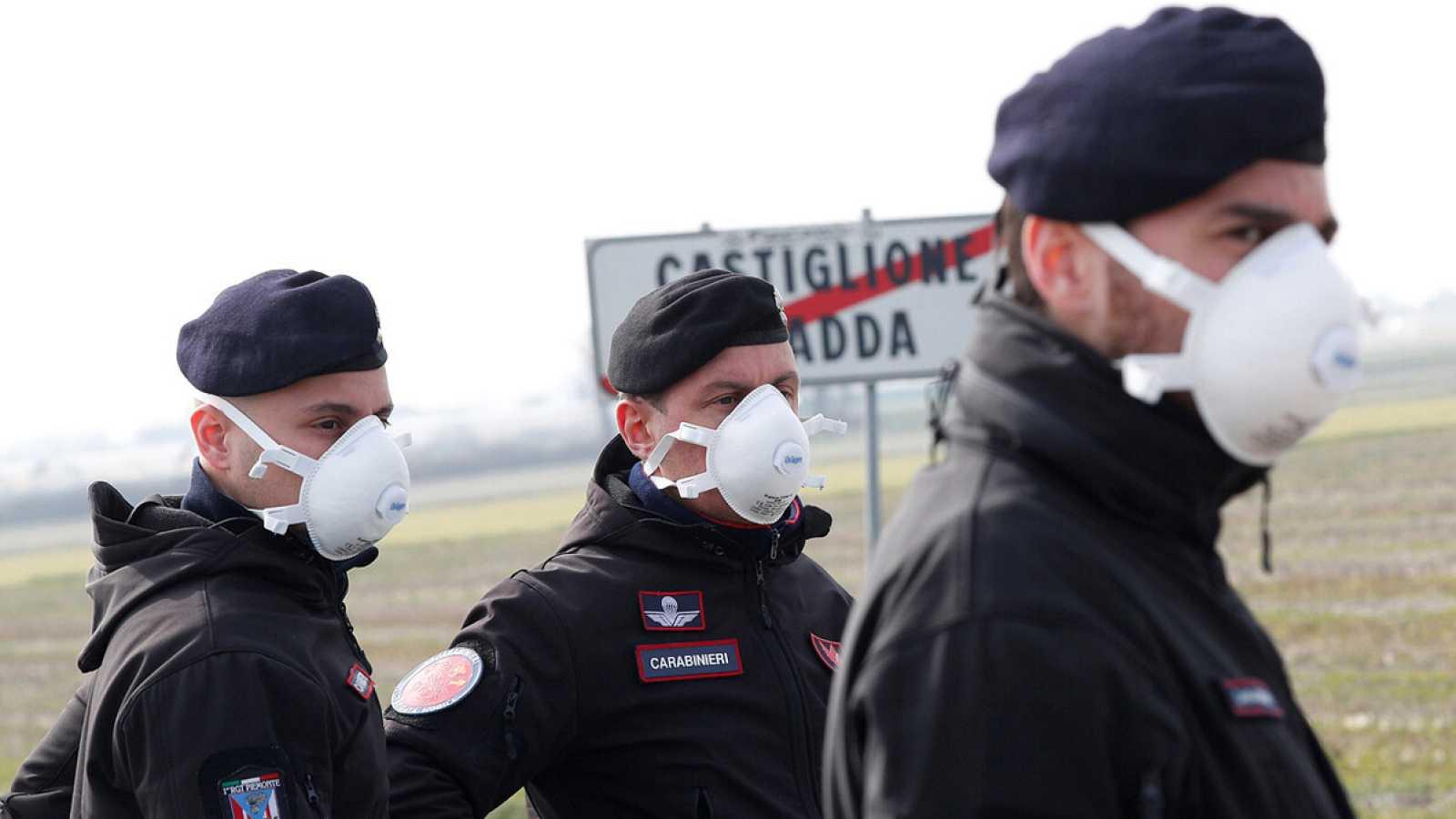 Oficiales de carabineros montan guardia con mascarillas por en Castiglione D'Adda, una de las localidades en cuarentena por el coronavirus,. REUTERS/Guglielmo Mangiapane