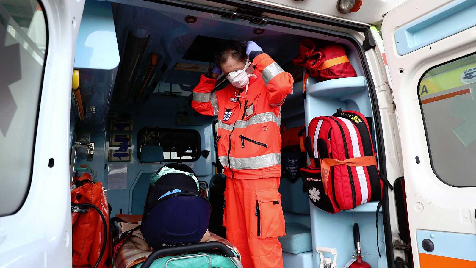 Un trabajador sanitario italiano se coloca una máscara de protección en una ambulancia.