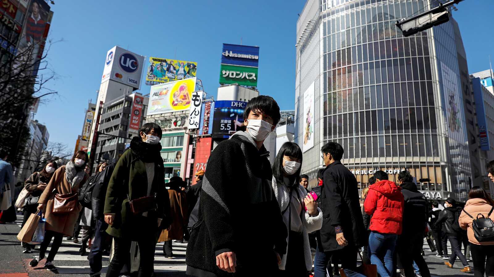 Personas llevando máscaras protectoras contra el coronavirus en el distrito comercial de Shibuya