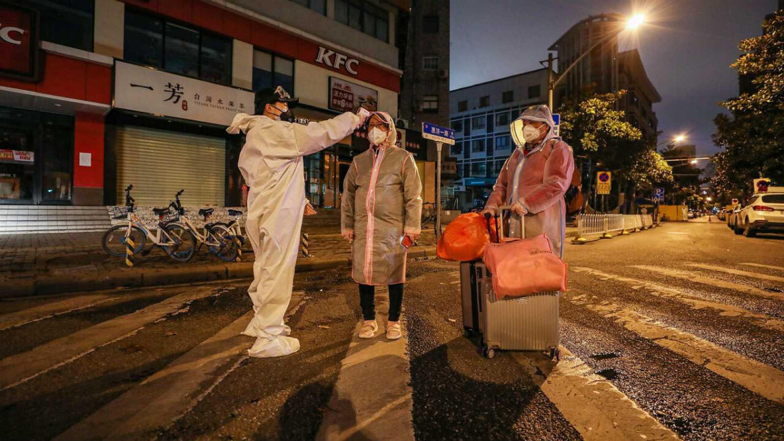 Un voluntario toma la temperatura y a acompaña a dos personas, una de ellas embarazada, al hospital de Wuhan.