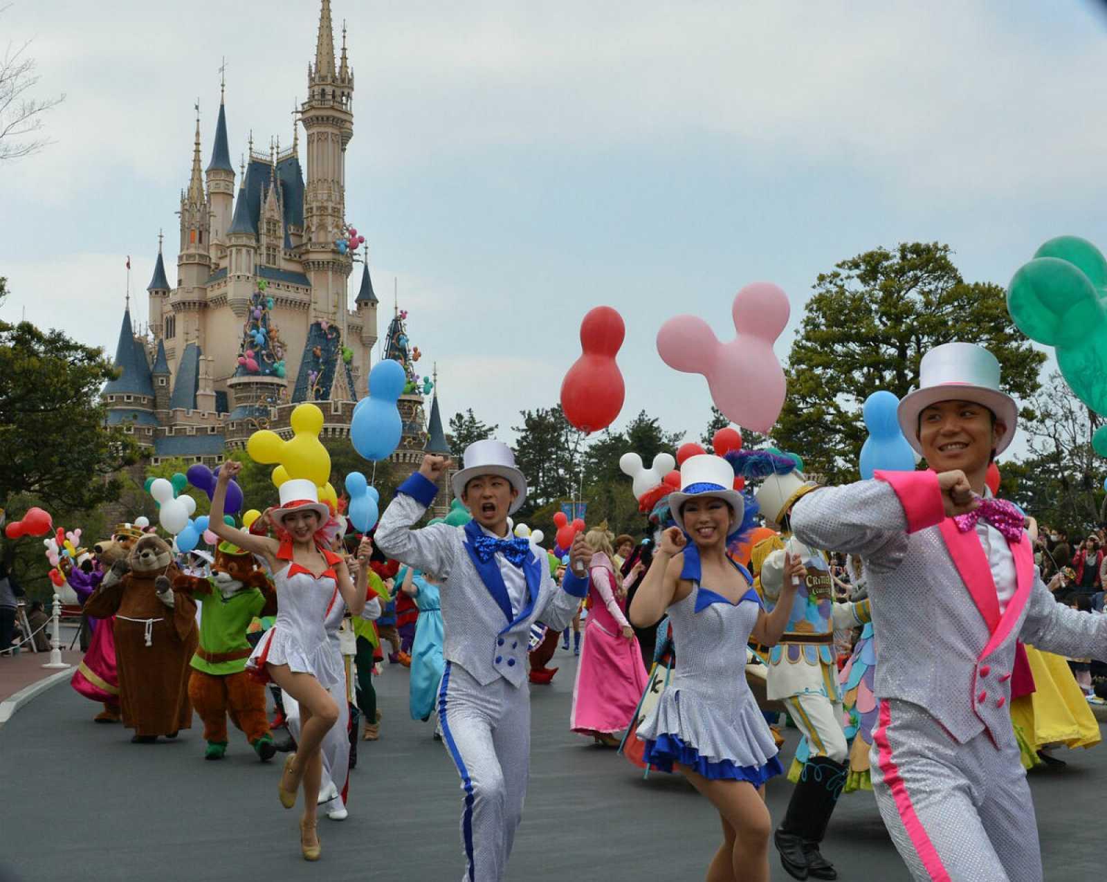 En esta imagen de archivo de 2013, personajes de la franquicia y bailarines desfilan, con el reconocido castillo al fondo.