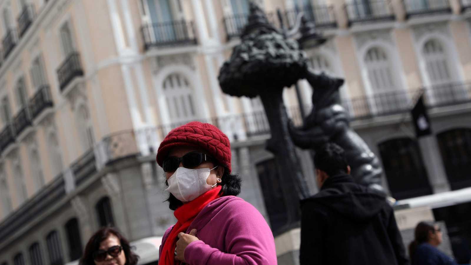 Una turista se protege con una mascarilla en la Puerta del Sol de Madrid