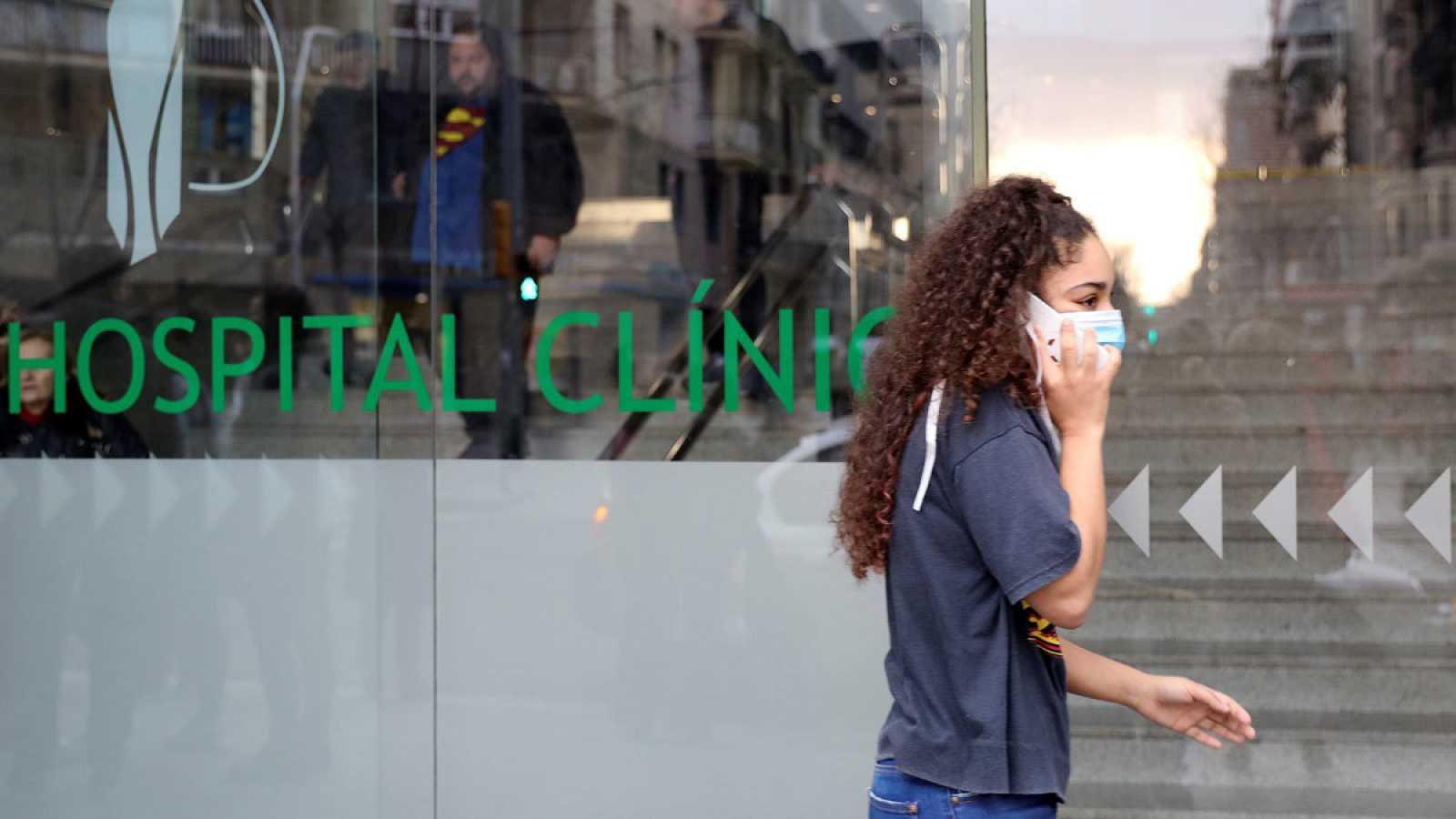 Un mujer con mascarilla pasa junto al Hospital Clinic en Barcelona