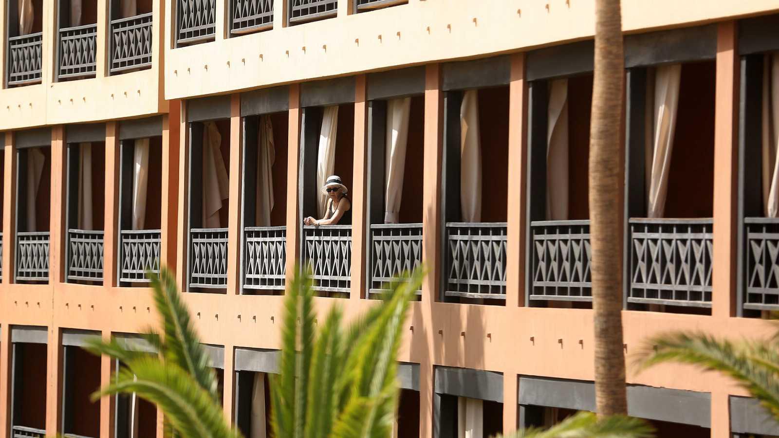Una turista se asoma al balcón de su habitación, en el hotel situado del sur de Tenerife, que se encuentra en cuarentena tras detectarse cuatro casos de coronavirus