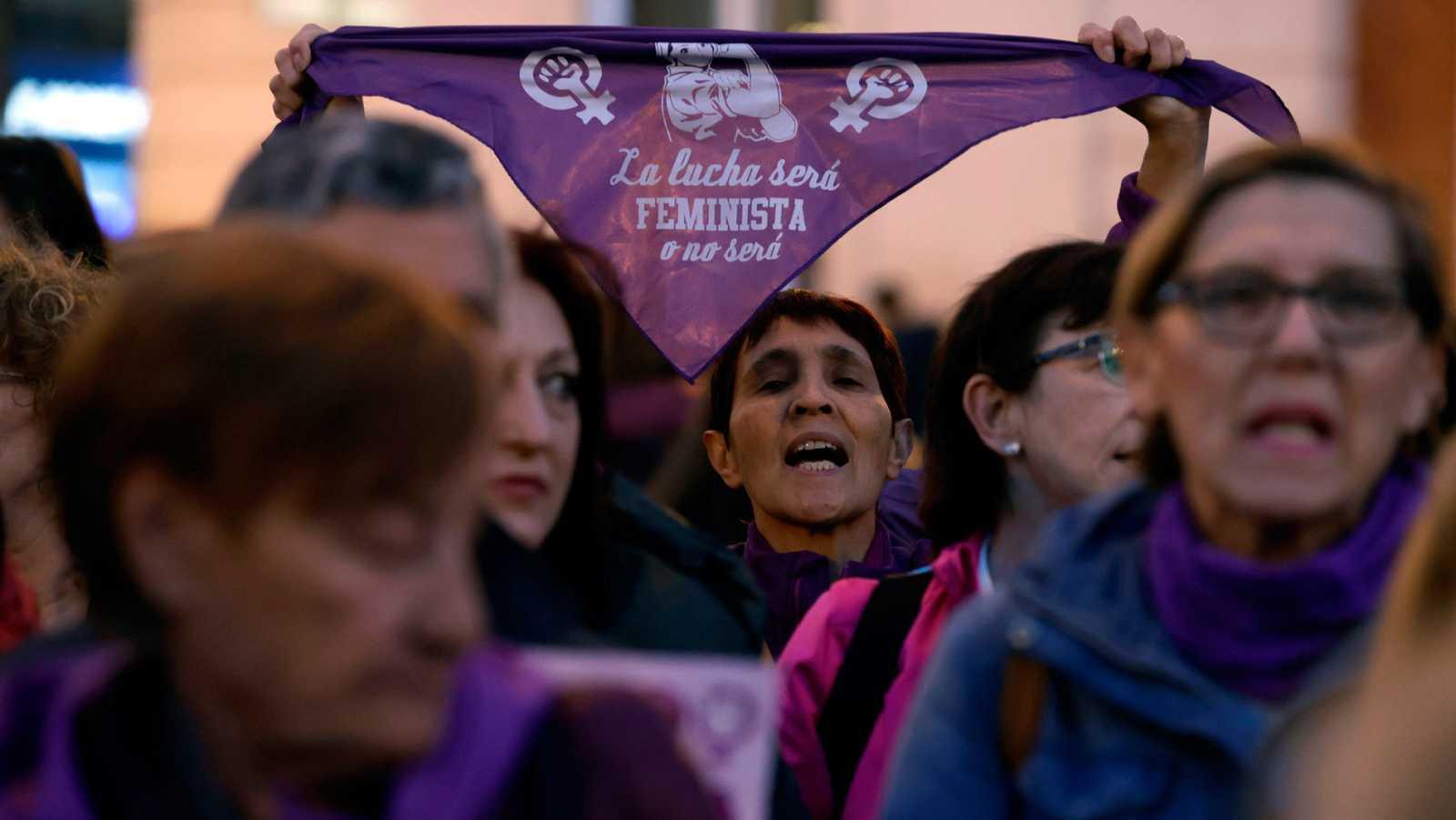 """Una mujer muestra un pañuelo violeta con el mensaje """"La lucha será feminista o no será"""" durante una concentración del Movimiento Feminista de Madrid."""