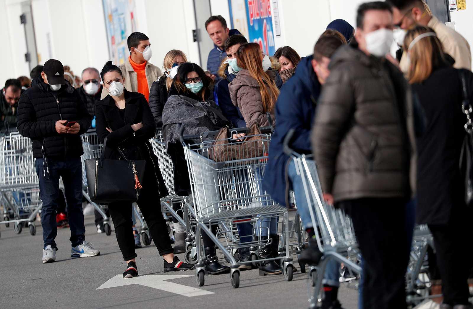 Varias personas hacen cola en un supermercado en el municipio italiano de Casalpusterlengo