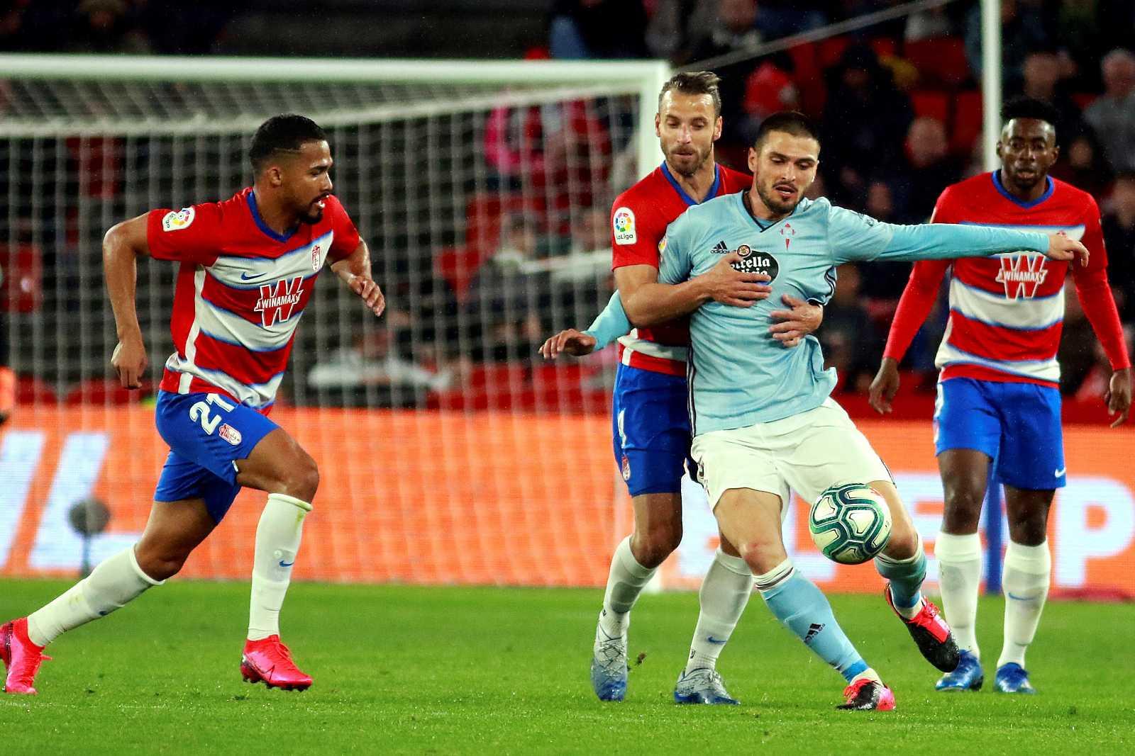 El delantero del Granada CF Roberto Soldado (2i) lucha con el turco Okay Yokuslu (2d), del Celta de Vigo, durante el partido