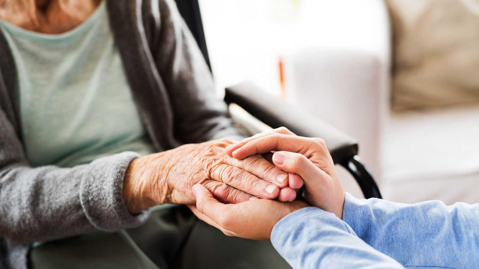 Un asistente asnitario sostiene las manos de una mujer dependiente durante una visita.