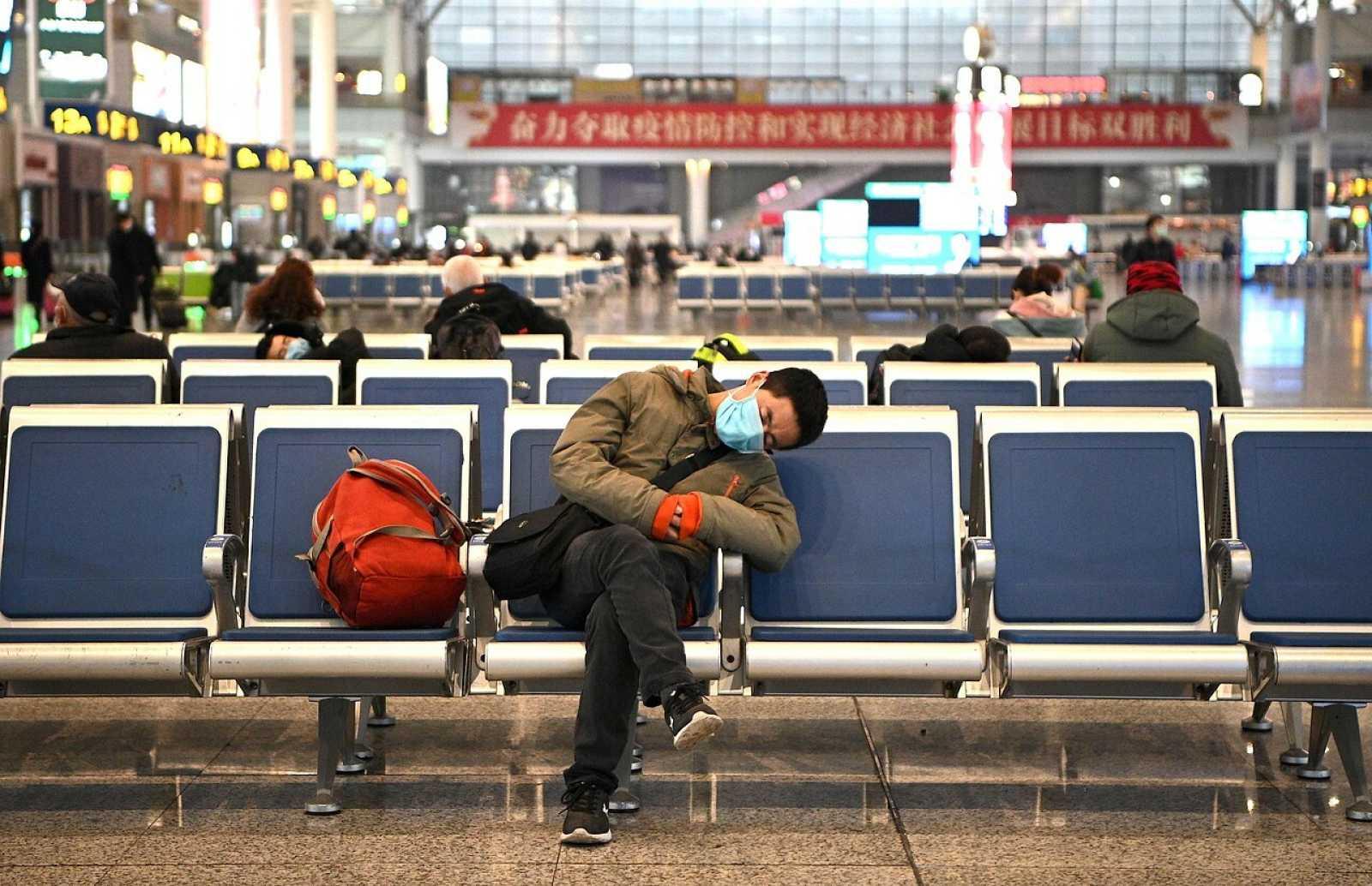 Un hombre duerme en la estación de Shangai con una mascarilla