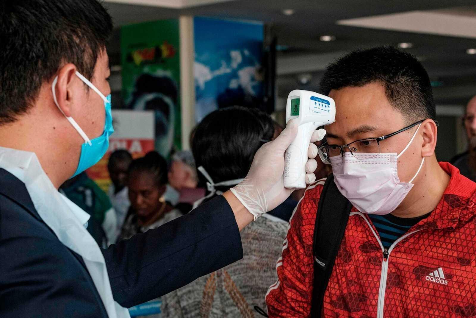 Un pasajero chino se toma la temperatura en un aeropuerto