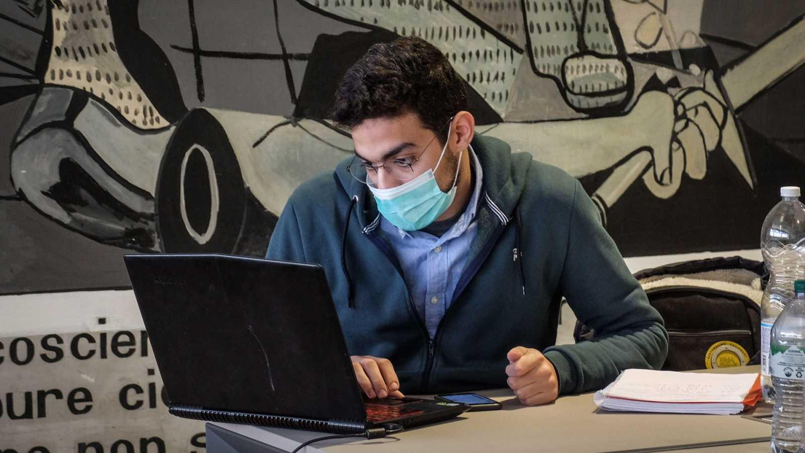 Un estudiante de la Universidad Politécnica de Milán se protege con mascarilla mientras estudia