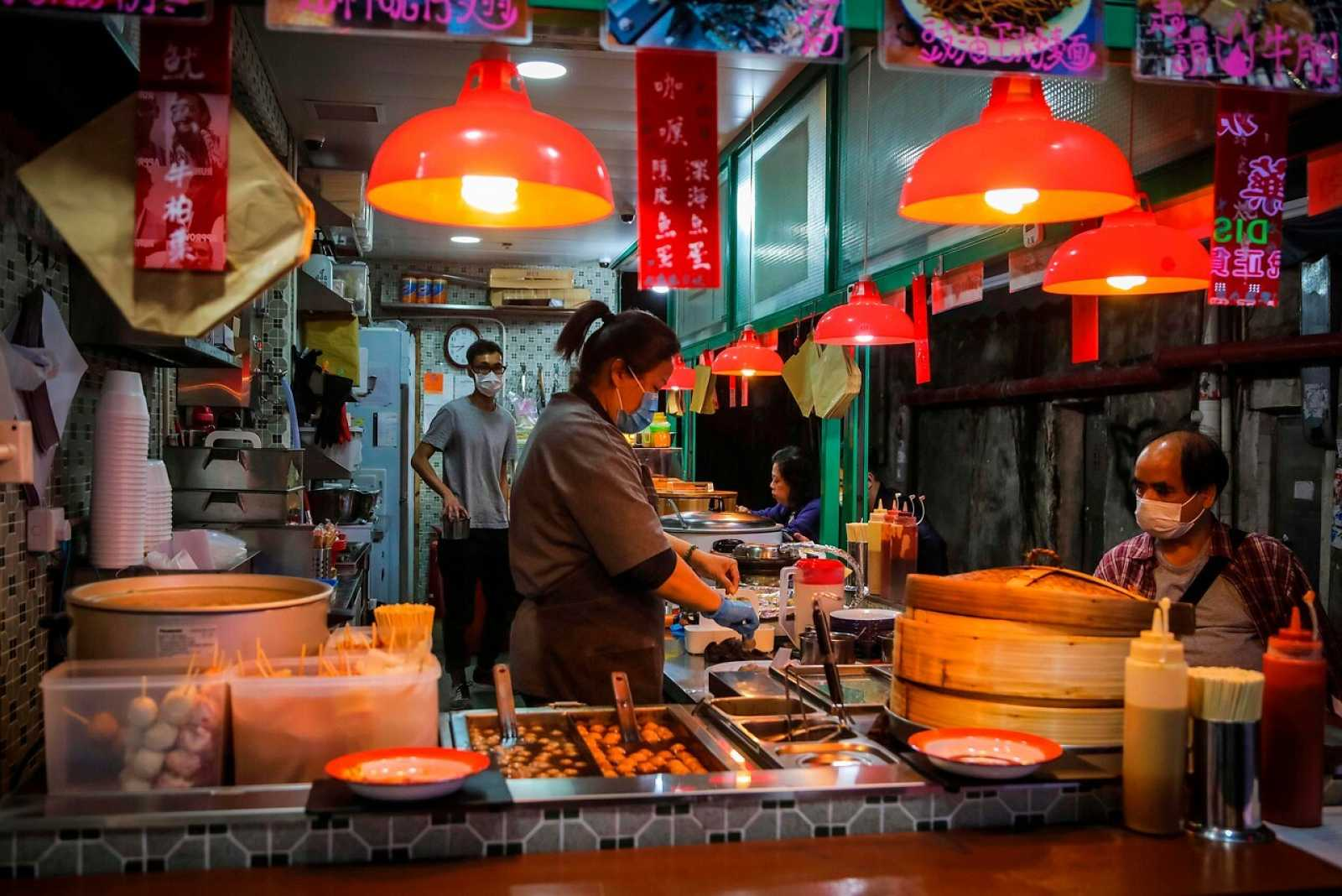 Trabajadores y consumidores utilizan mascarillas en un mercado de Hong Kong