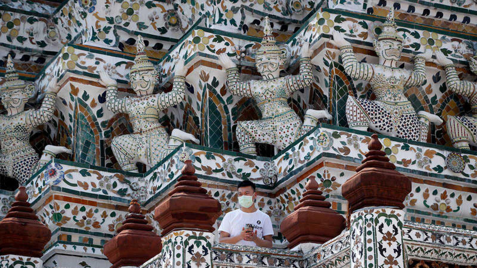 Un turista chino visita el Templo del Amanecer (Wat Arun) de Bangkok portando una mascarilla