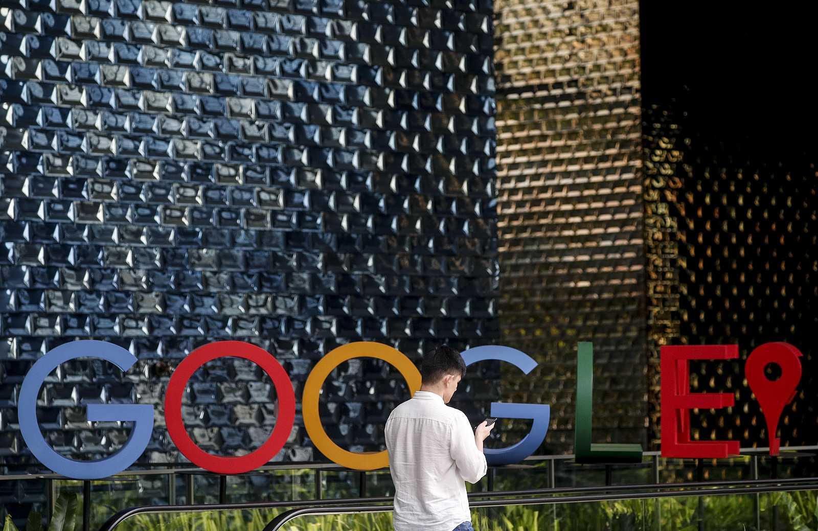 Singapur. Hombre usando su teléfono móvil mientras camina ante el logo de Google en Singapur