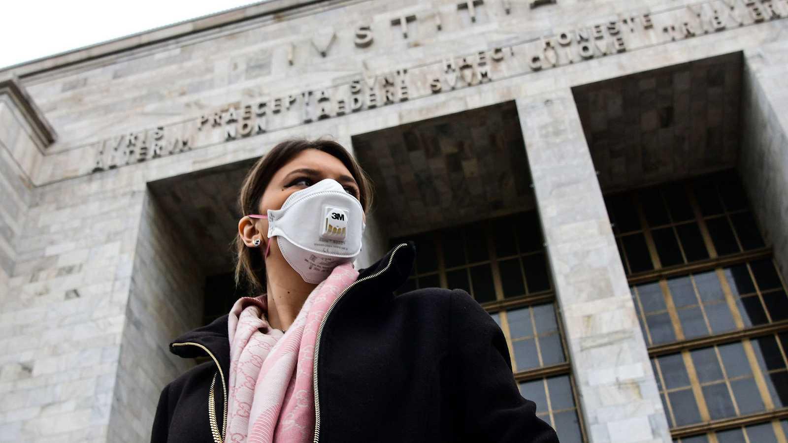 Una mujer con mascarilla camina frente al Palacio de Justicia de Milán.