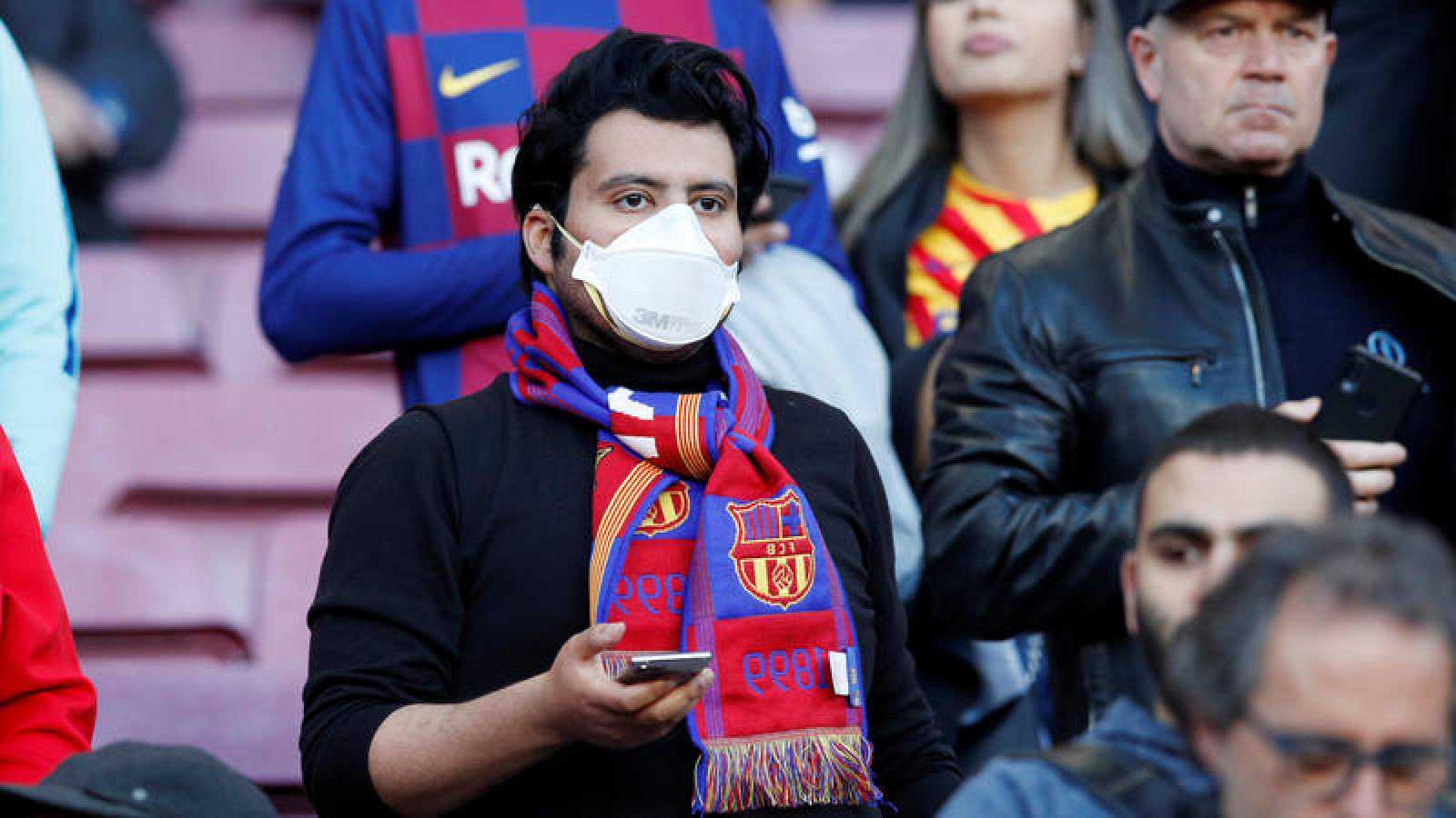 Aficionado del FC Barcelona con mascarilla para evitar la propagación del coronavirus