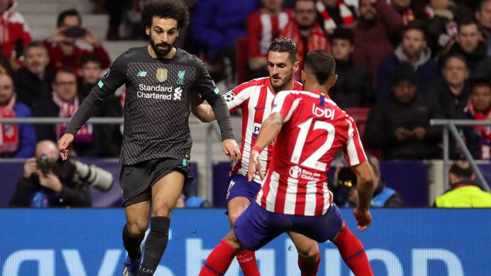 El delantero del Liverpool Mohamed Salah intenta escaparse de los jugadores del Atlético Renan Lodi y Koke.