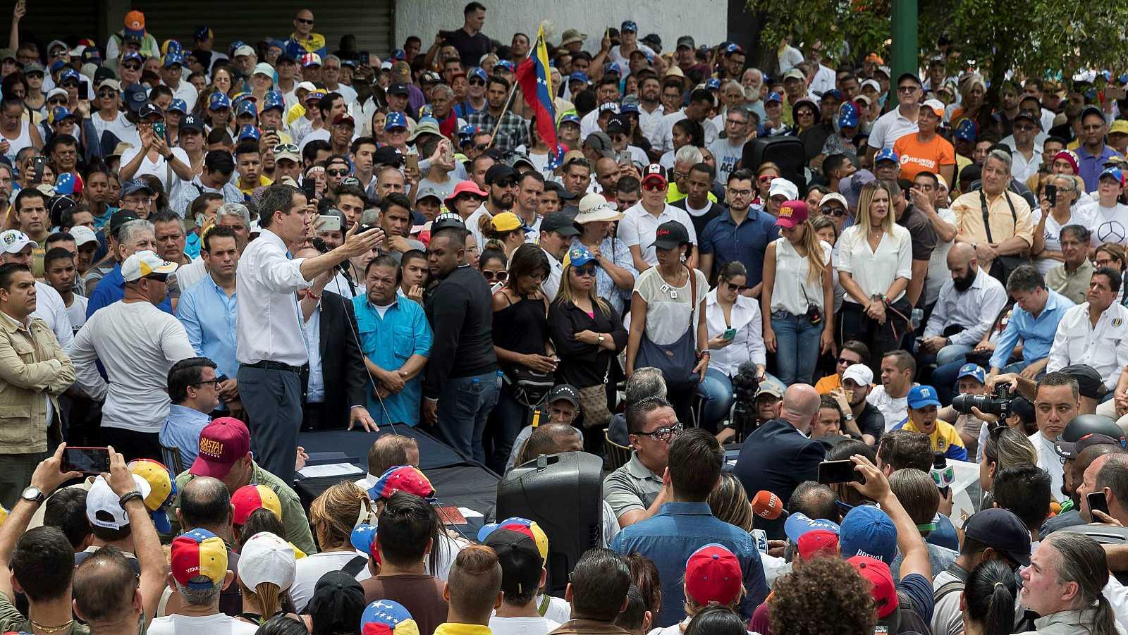 Guaidó en un discurso con un megáfono en una de las archas en Caracas rodeado de personas