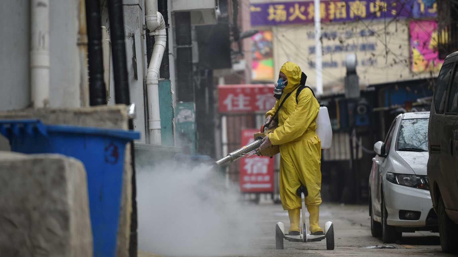Un sanitario desinfecta un barrio residencial en Wuhan