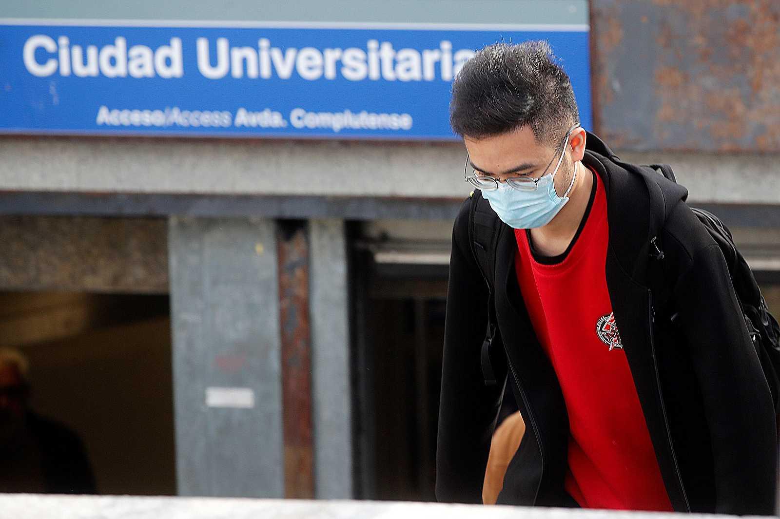 Un joven con mascarilla en el acceso a la estación de metro de Ciudad Universitaria