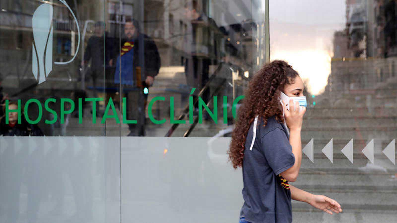 Una joven con mascarilla pasa delante del Hospital Clínic de Barcelona