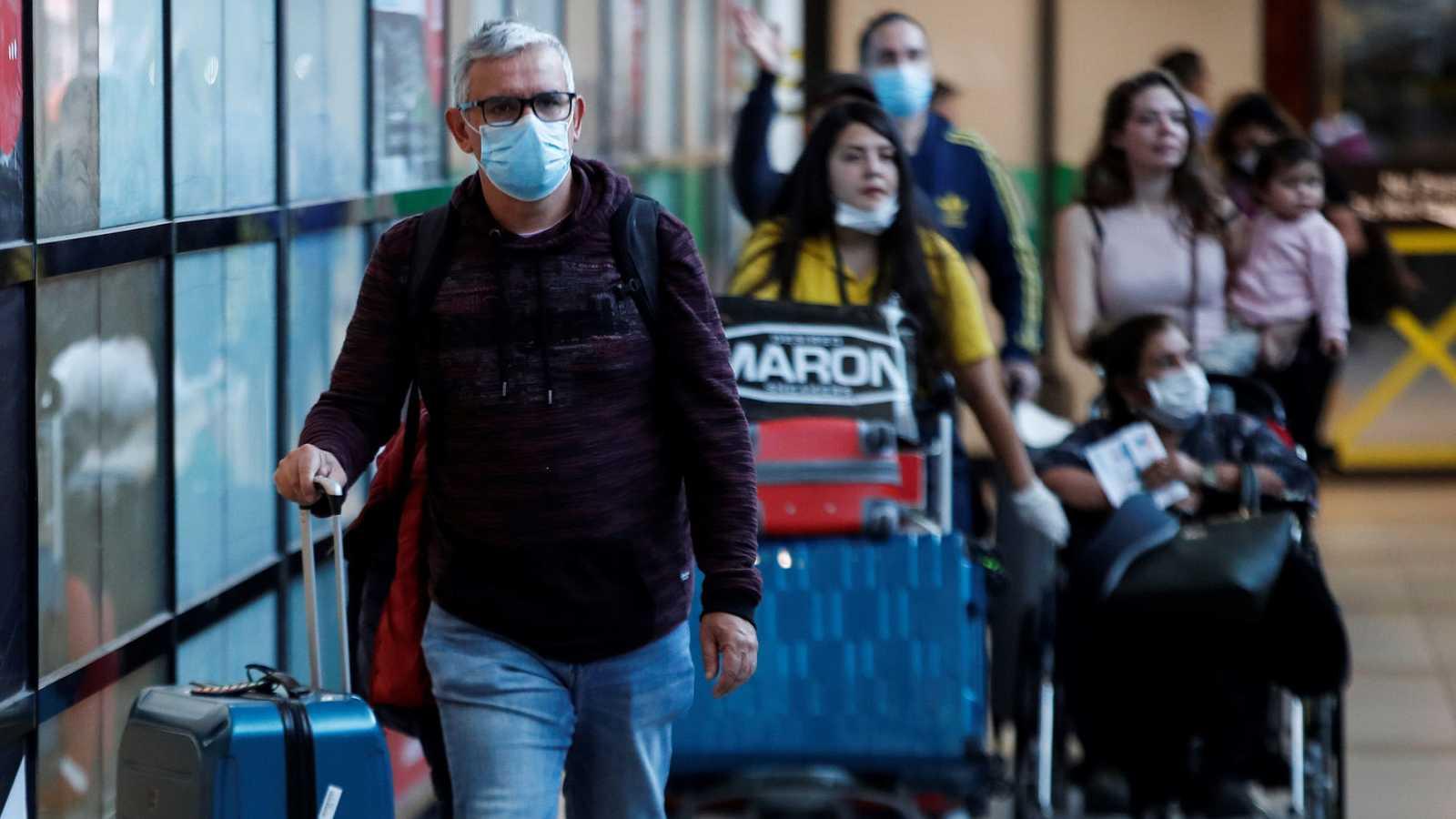 Pasajeros usando mascarillas para evitar la propagación y el contagio del coronavirus en el aeropuerto