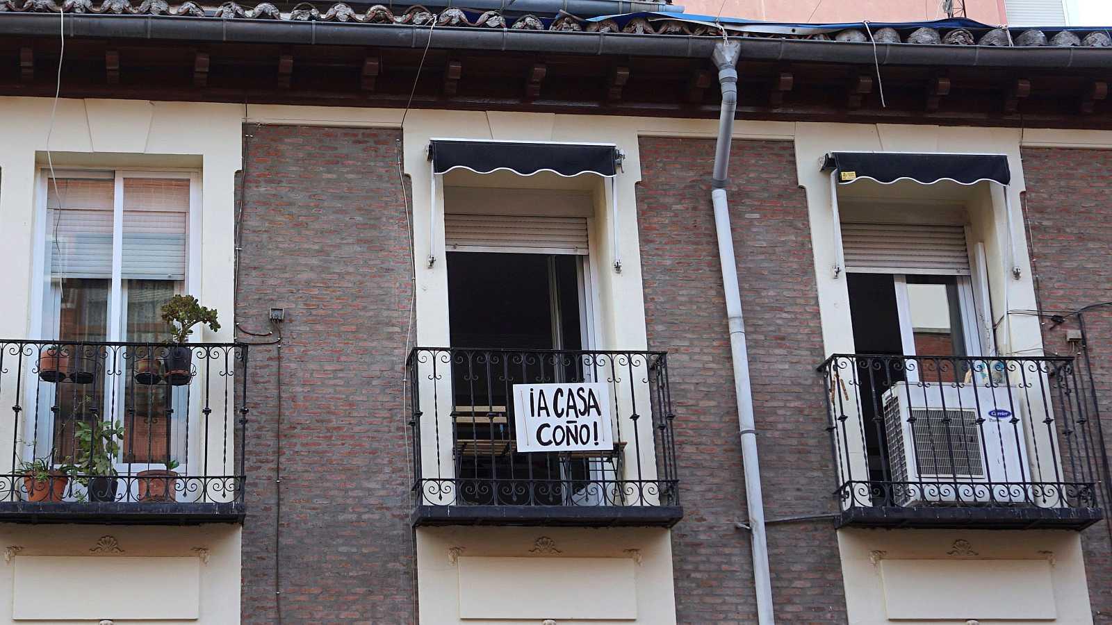 Un cartel colgado en un balcón pide a sus vecinos que se queden en casa para evitar los contagios.
