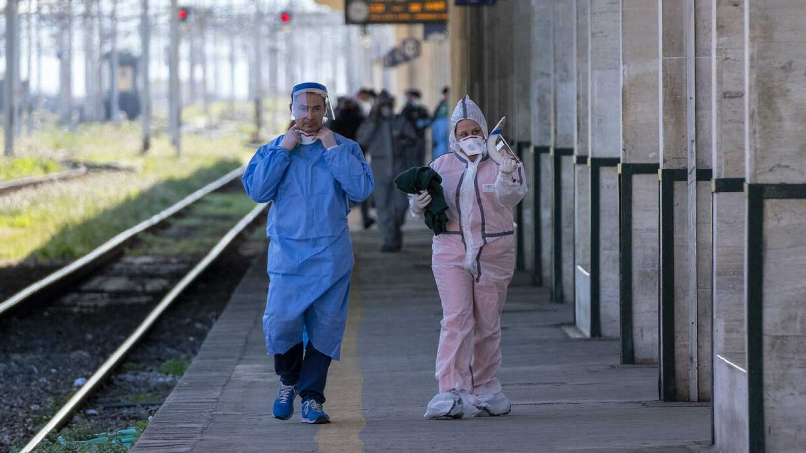 Personal de una estación de trenes de Italia con trajes especiales para protegerse el coronavirus.