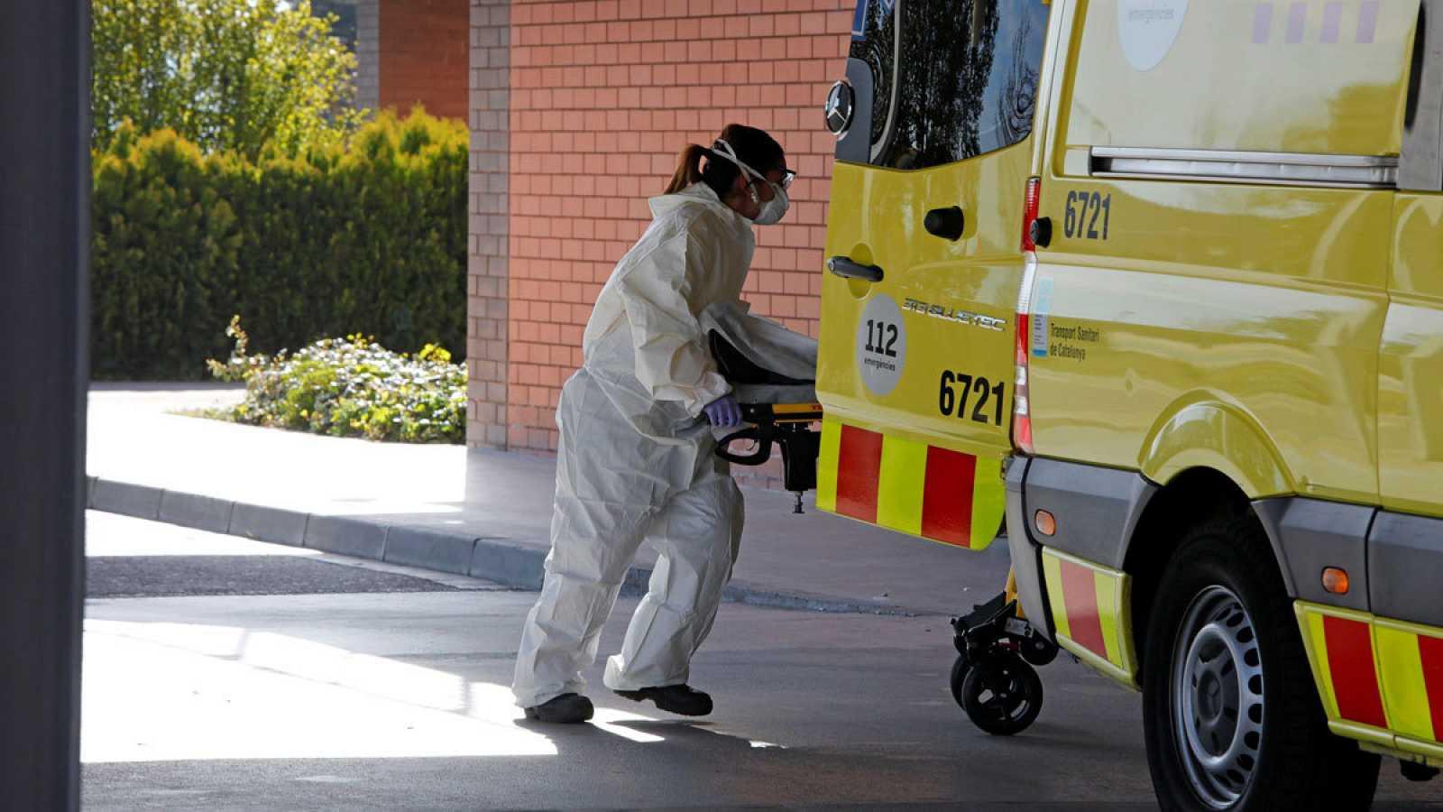 Una trabajadora de urgencias introduce una camilla en una ambulancia