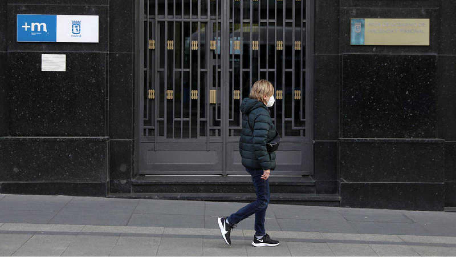 Una mujer pasea por Madrid portando una mascarilla protectora