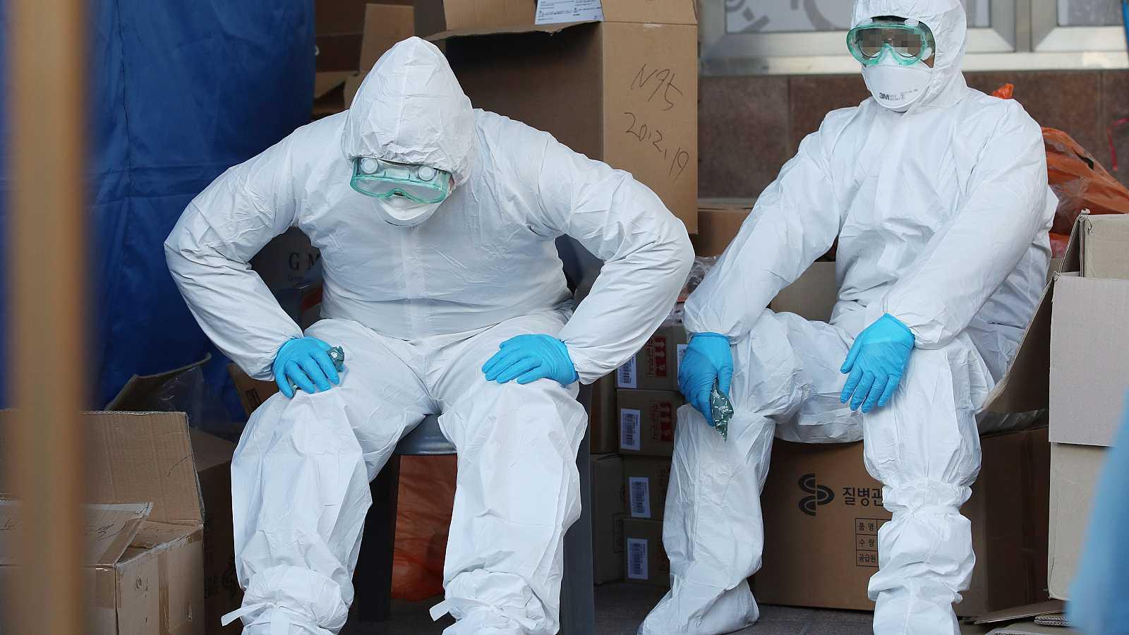 Dos trabajadores sanitarios surcoreanos descansan después de realizar decenas de pruebas para el coronavirus.