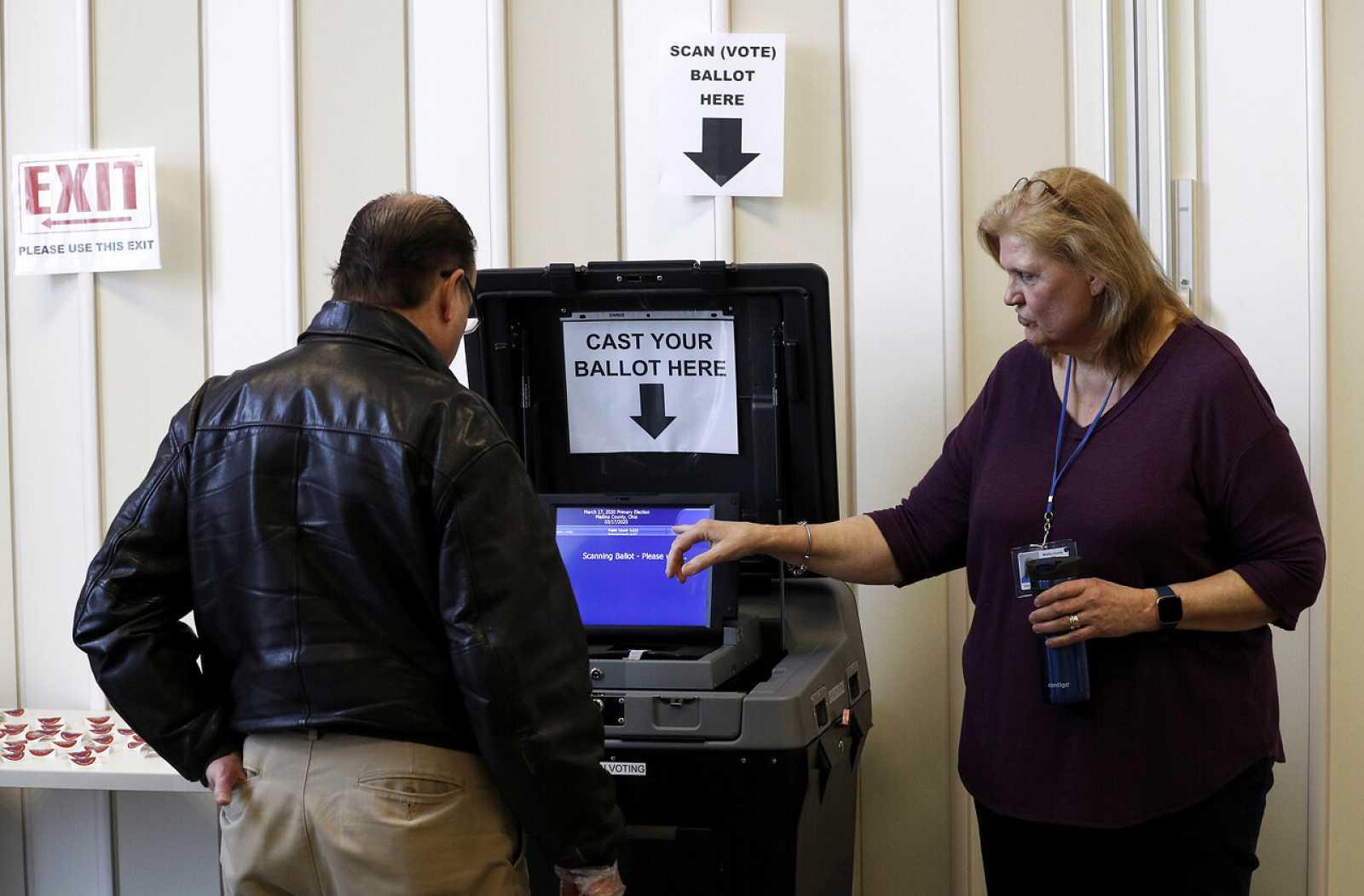 Una voluntaria ayuda a un hombre a emitir su voto anticipado en Medina, Ohio