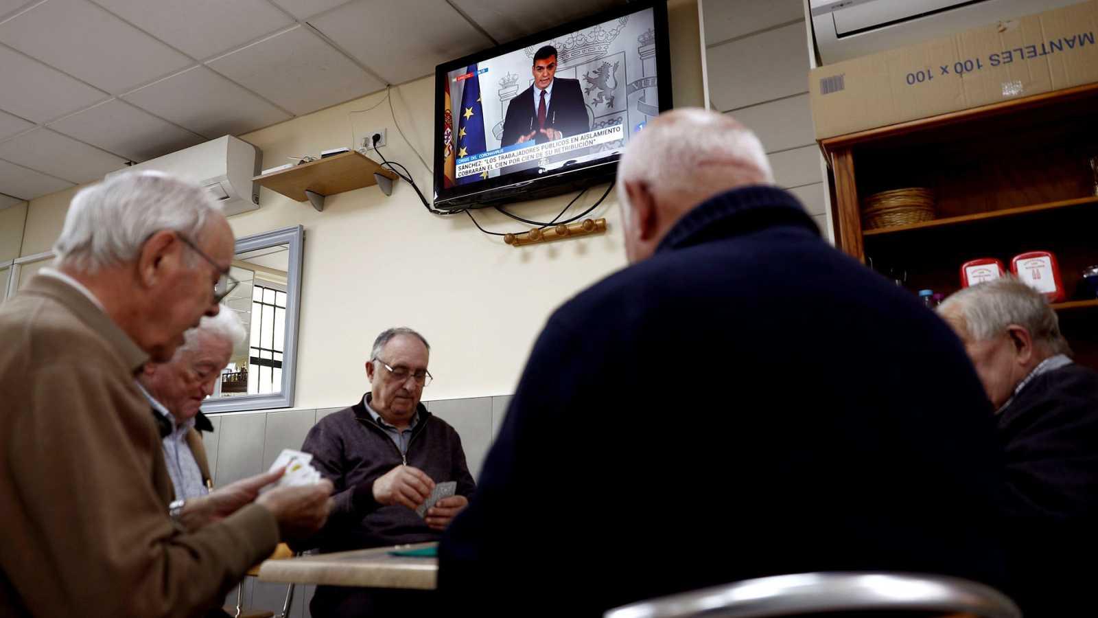 Un grupo de ancianos juega a las cartas en un bar del barrio de Aluche, en Madrid