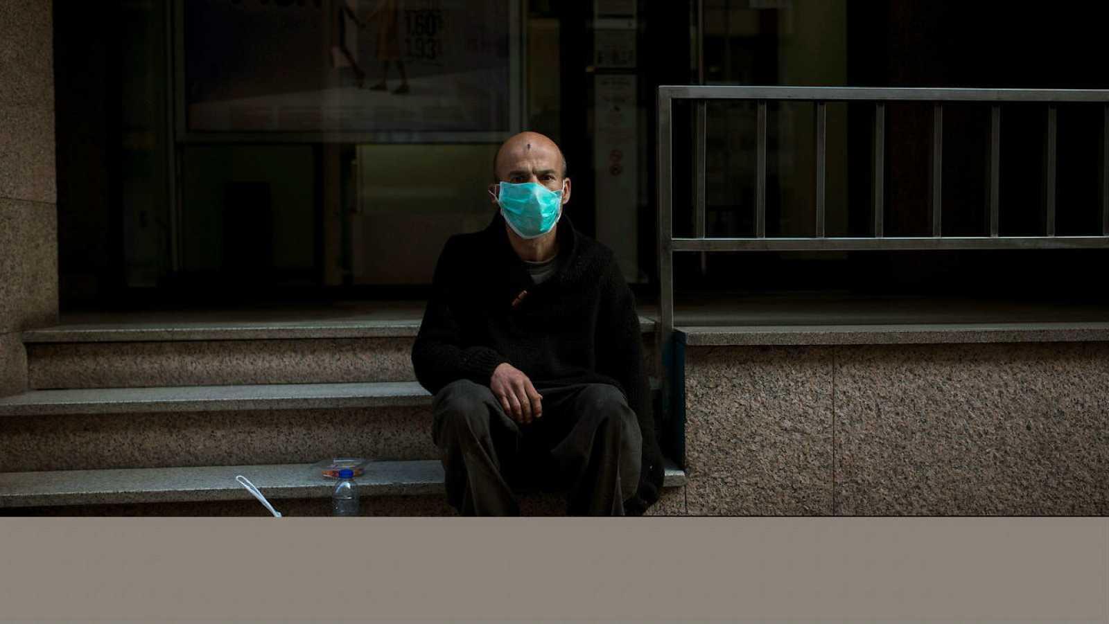 Un hombre con mascarilla sentado en la calle para protegerse del coronavirus.