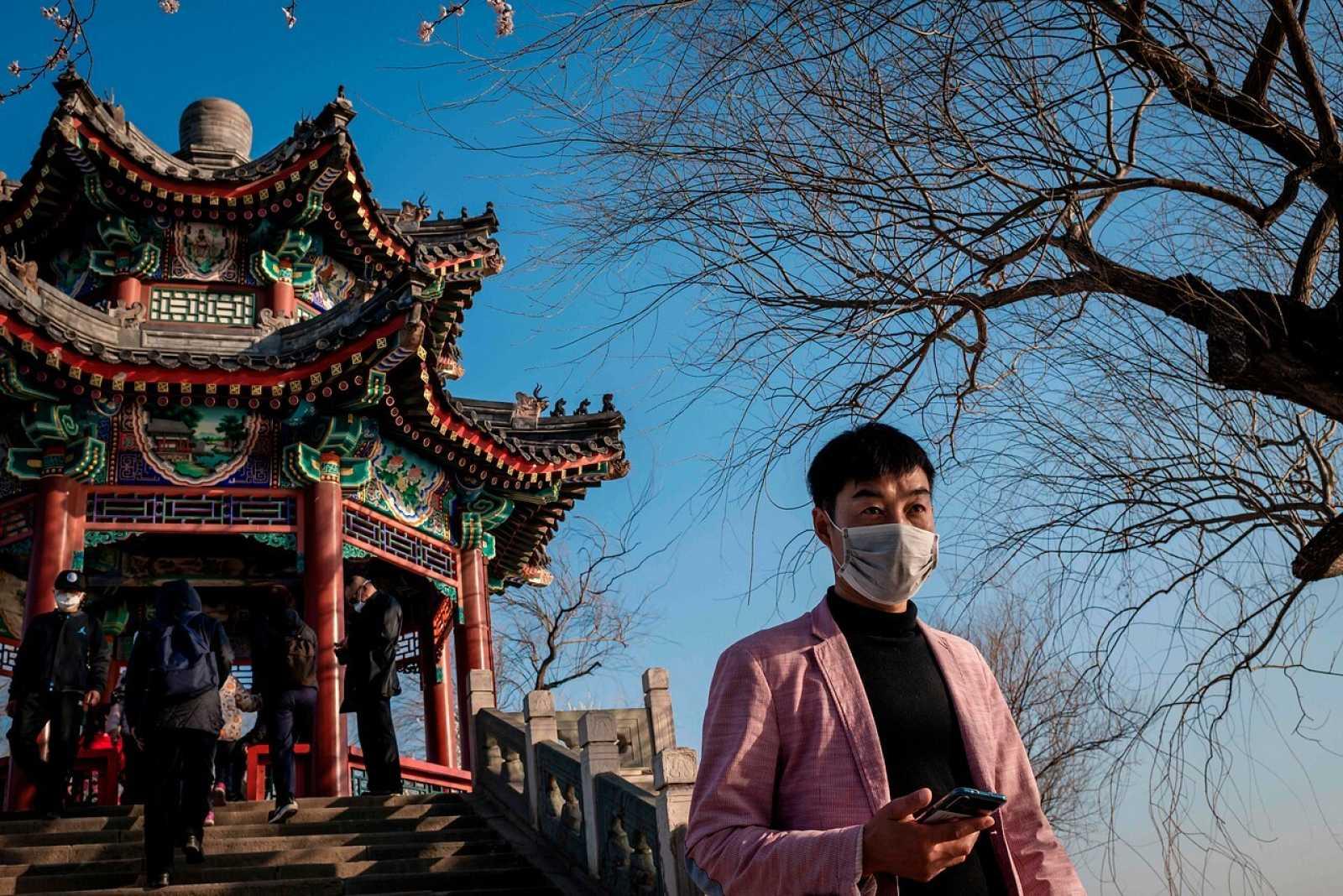 Un hombre con mascarilla camina ante el Palacio de Verano de Pekín