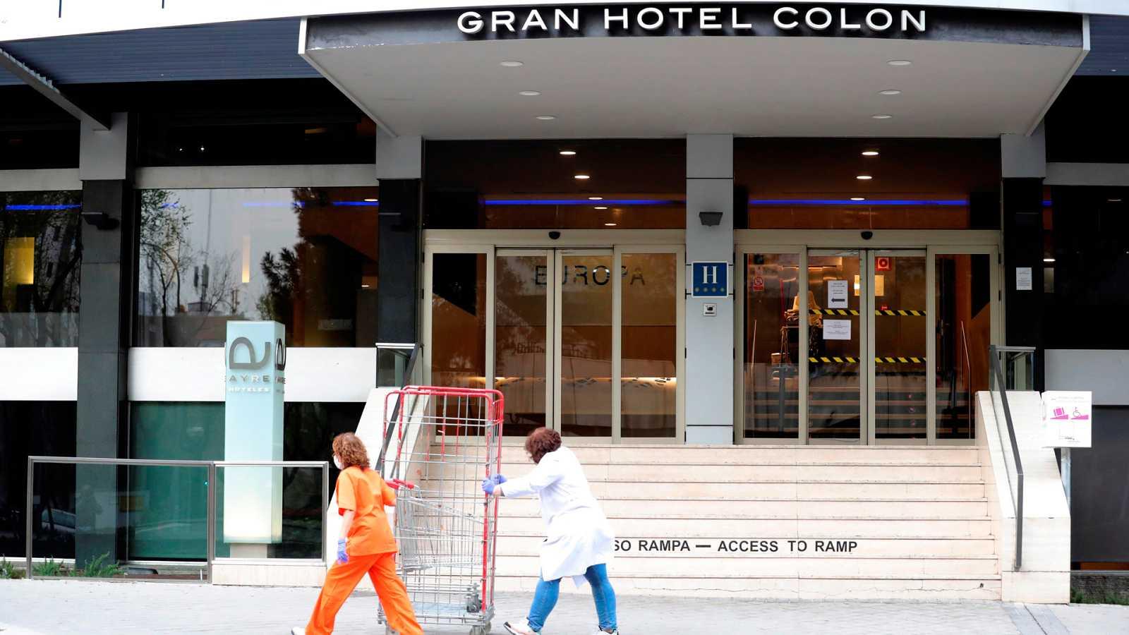 Dos empleadas con máscaras sanitarias pasan frente al hotel Gran Hotel Colon de la cadena Ayre