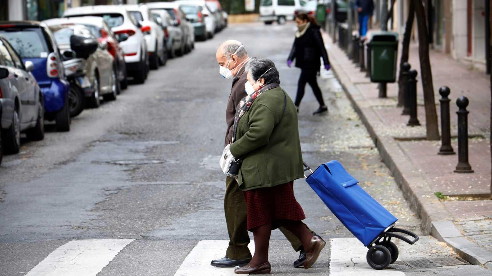Dos personas mayores van a la compra protegidas con mascarillas