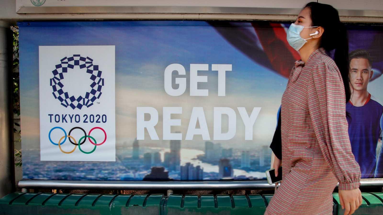 Una mujer pasa por delante de un cartel de los Juegos Olímpicos de Tokio