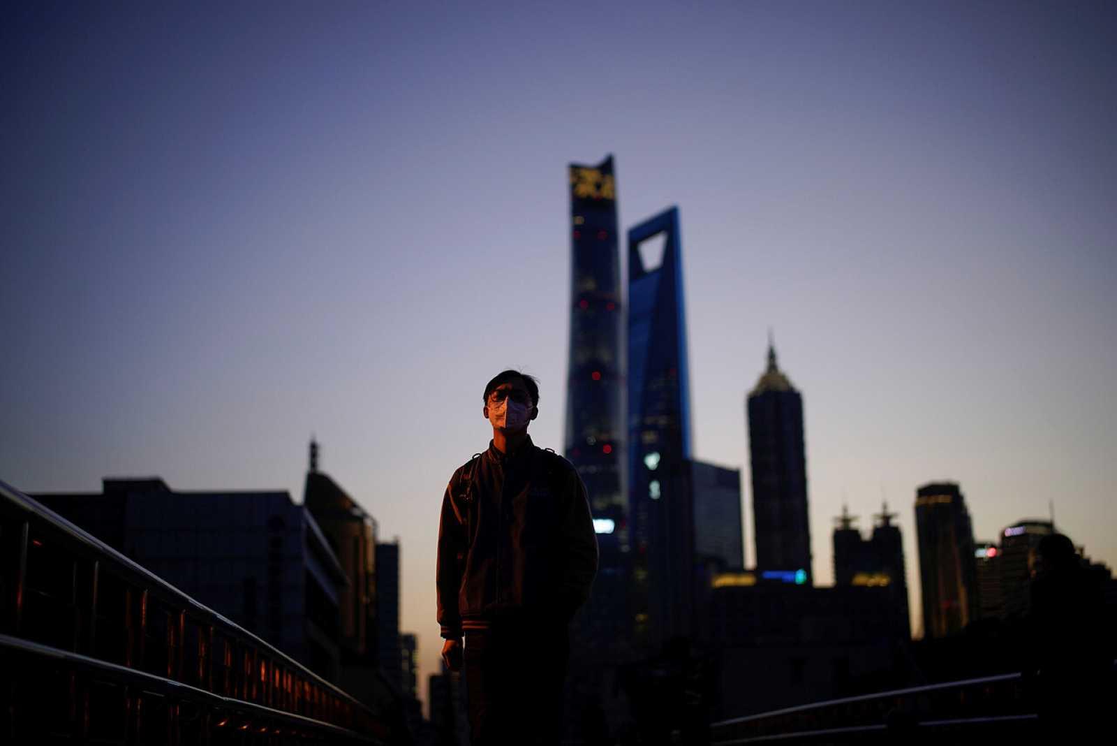 Un hombre usa una máscara en el distrito financiero de Lujiazui en Shanghái, China