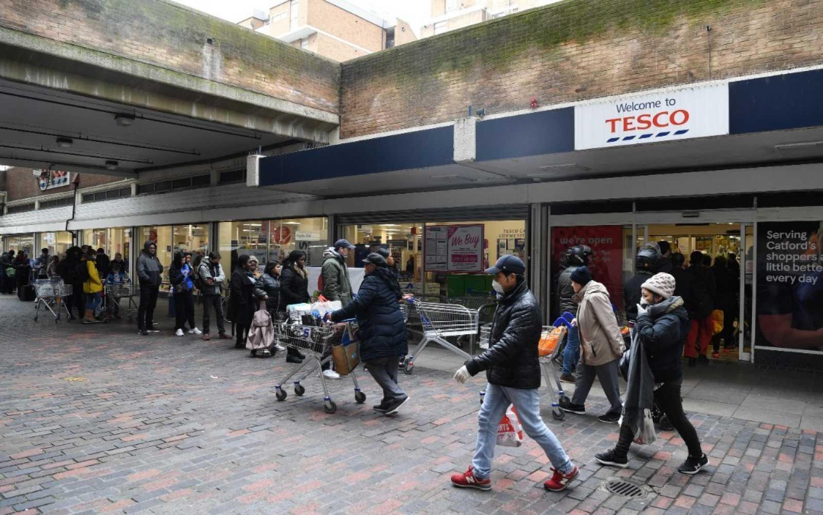 Gente esperando en fila para hacer la compra en un supermercado en el sur de Londres, Reino Unido