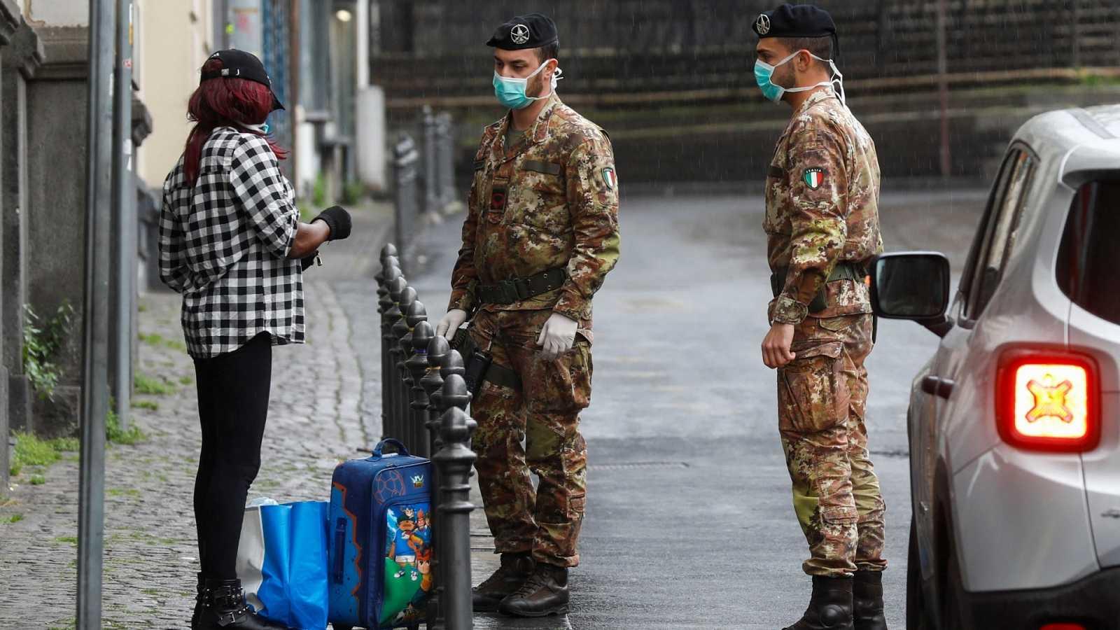 Soldados italianos piden su identificación a una viandante en Catania.