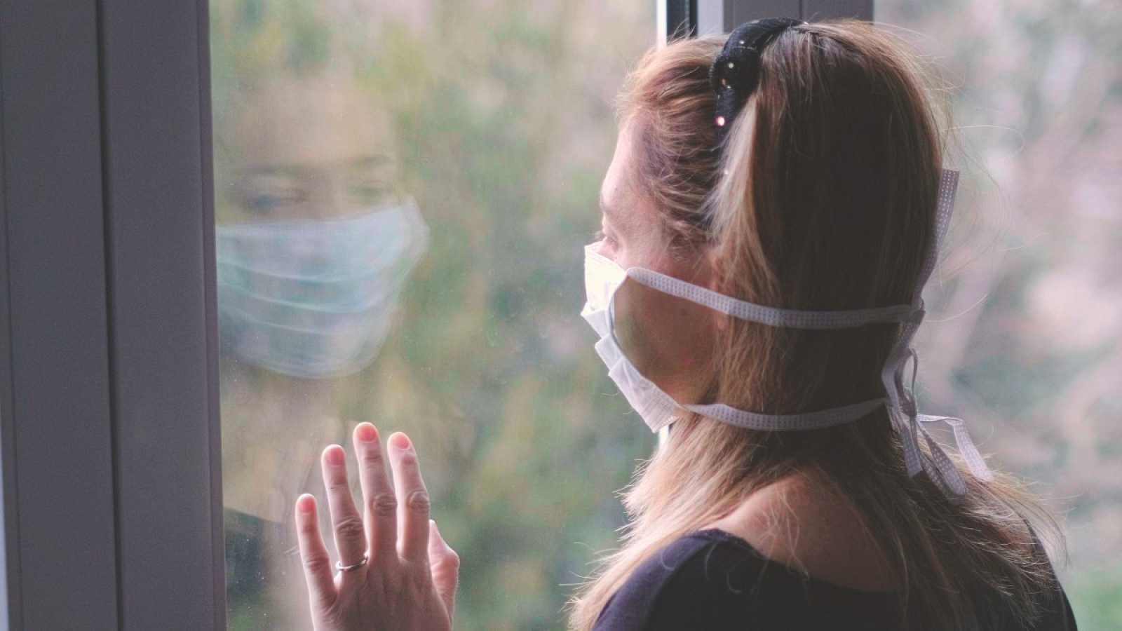 Una mujer aislada en casa mira a través de la ventana